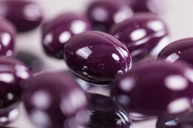 Cápsulas púrpura closeup comprimidos na superfície do espelho
