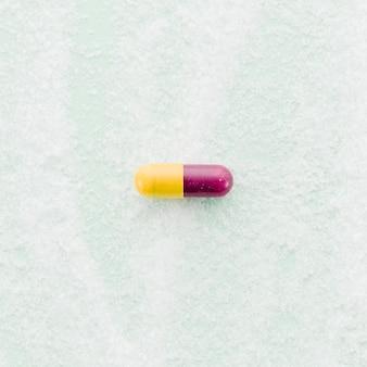 Cápsulas vermelhas e amarelas no pano de fundo texturizado
