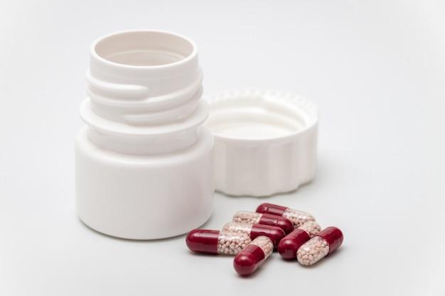 Cápsulas vermelhas e brancas com garrafa de plástico em branco
