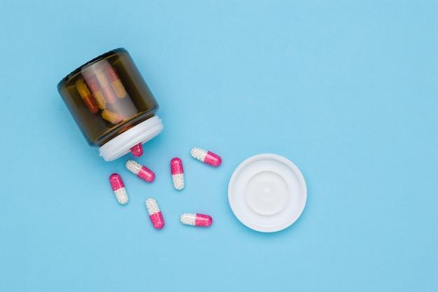 Cápsulas vermelhas e brancas com medicamento em uma colher de pau em uma superfície azul