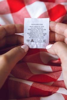 Captura de close-up de uma mulher verificando o rótulo do cuidado mostrando instruções de lavagem com símbolos.