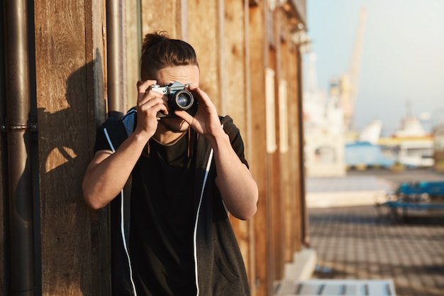 Capturando todos os momentos da vida. foto ao ar livre do jovem fotógrafo elegante olhando através da câmera vintage, tirando fotos do porto, iates e beira-mar, trabalhando como operador de câmera freelancer