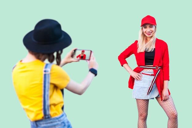 Capture o momento. duas garotas elegantes e hipster em roupas da moda se divertindo juntas, mulher morena fazendo fotos de sua melhor amiga, humor positivo de amizade, fotógrafo no trabalho, interior
