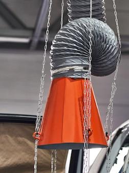 Capuz de um extrator de ar industrial na oficina de reparação automóvel