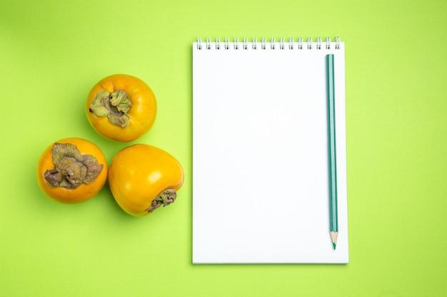 Caqui caqui lápis lápis caderno branco na mesa verde