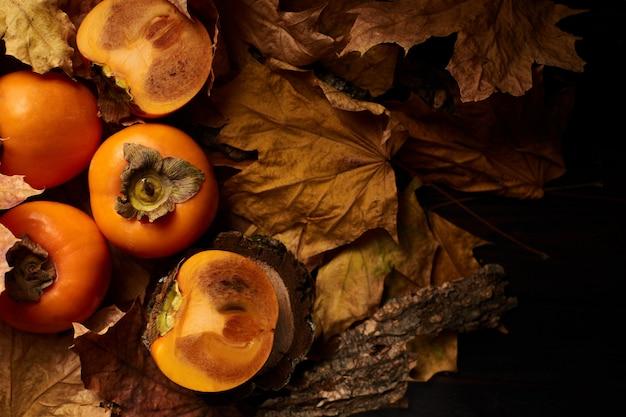Caqui fatiado fresco frutas em folhas de outono laranja na madeira