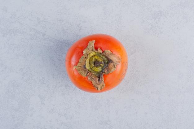 Caqui laranja fresco orgânico em fundo cinza.