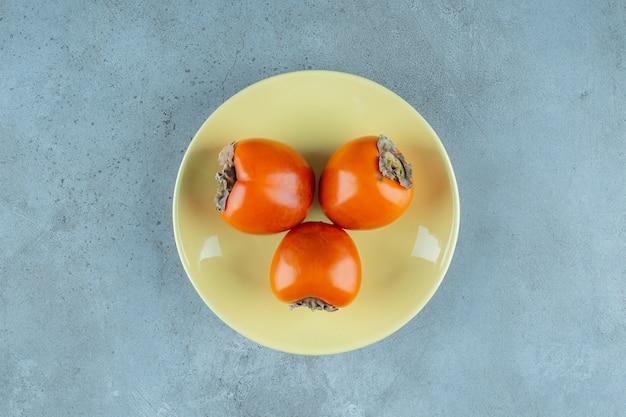 Caqui maduro em um prato, no fundo de mármore. foto de alta qualidade