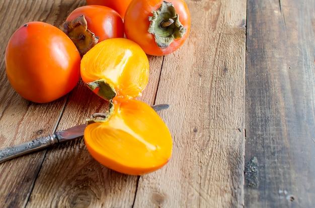 Caquis de laranja maduros sobre uma velha mesa de madeira