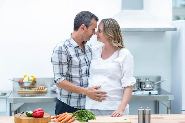 Cara a cara com mulher grávida em sua cozinha
