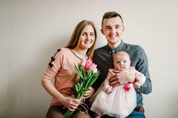 Cara, a mulher abraça a garotinha. pai segura pequeno buquê de mãe parabéns menina bebê de tulipas cor de rosa de flores. conceito de dia das mães