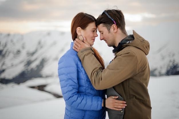 Cara abraça uma garota contra uma cena de montanhas cobertas de neve cinza