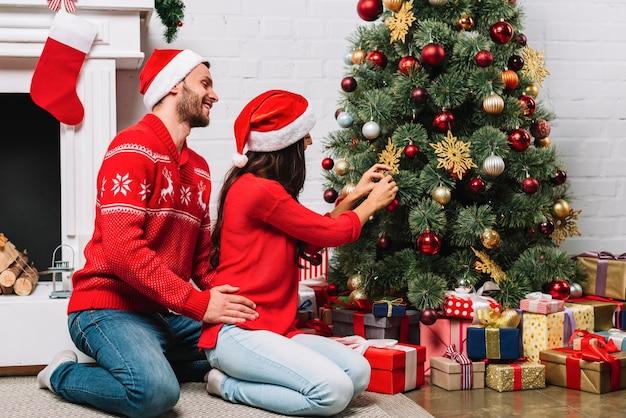 Cara abraçando a senhora decorando a árvore de natal com enfeites