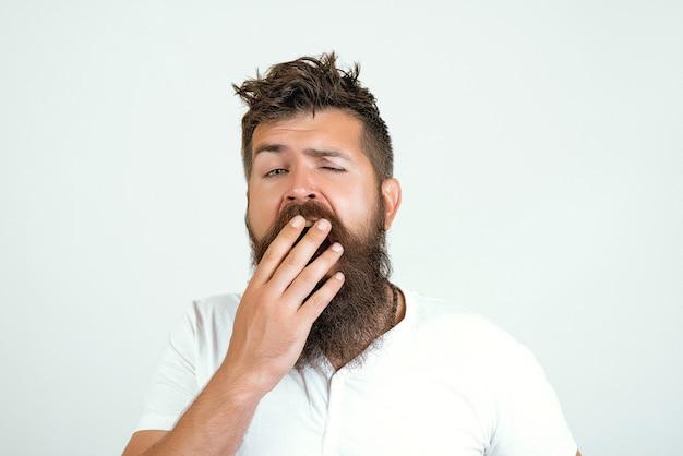 Cara acorda com a boca aberta em um bocejo, copie o espaço. manhã e acorda, vida cotidiana. homem com cara de sono bocejando em fundo branco. hipster com barba com cabelo bagunçado. conceito de bocejo de manhã.