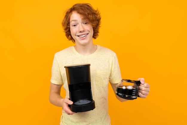 Cara adolescente com uma máquina de café e uma caneca de café em um fundo amarelo
