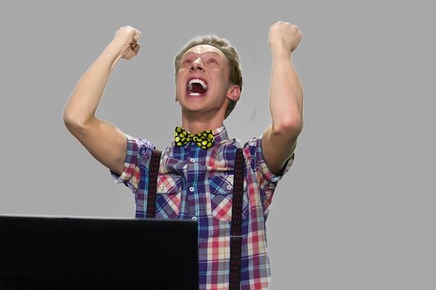 Cara adolescente expressivo chocado comemorando a vitória. rapaz adolescente animado com o computador portátil comemorando o sucesso. conceito de expressão do vencedor.