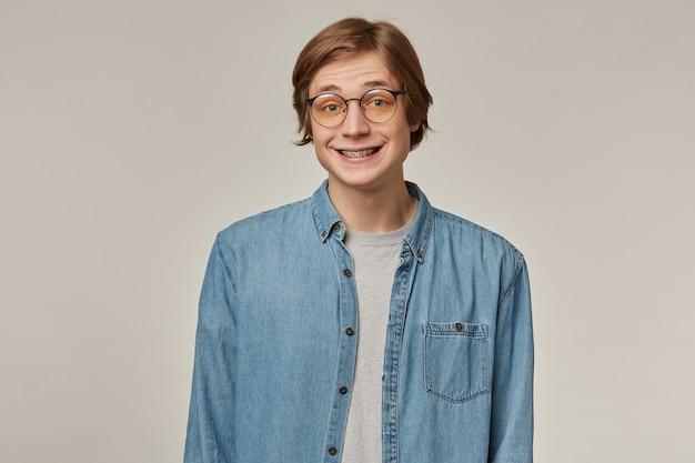 Cara adolescente, homem de aparência feliz com cabelo loiro. vestindo camisa jeans azul, óculos e suspensório. encolhe os ombros e sorri. conceito de emoção.