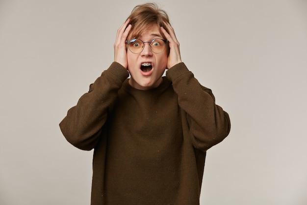 Cara adolescente, homem de aparência feliz com cabelo loiro. vestindo óculos e suéter marrom. tem colchetes.