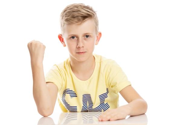 Cara adolescente mostra um punho enquanto está sentado à mesa. isolado sobre o fundo branco