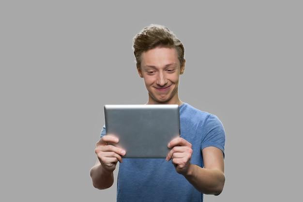 Cara adolescente usando tablet digital contra um fundo cinza. menino caucasiano sorridente, tendo a chamada de vídeo.