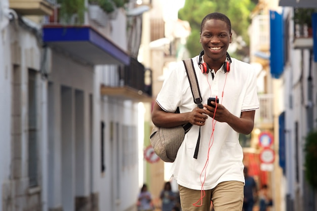 Cara africana andando na rua com um telefone