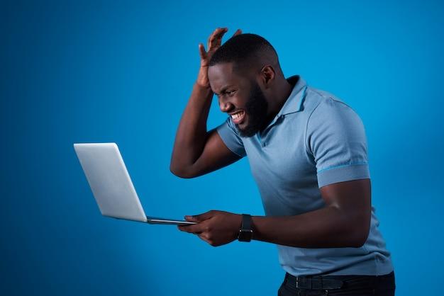 Cara africana com laptop e segurando sua cabeça