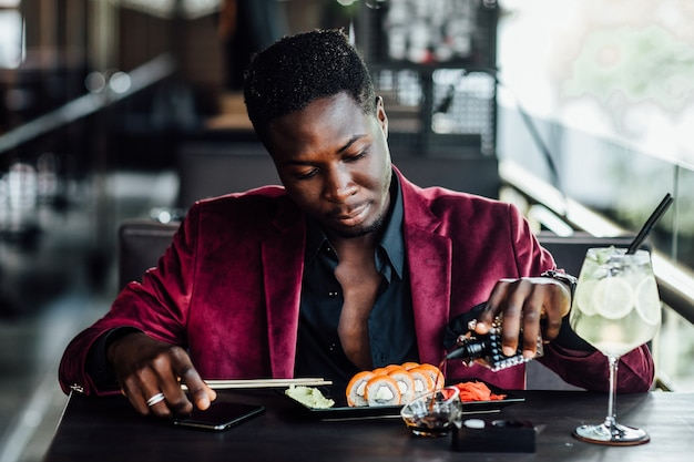 Cara africano encaracolado alegre segurando rolos de sushi de pauzinhos. terraço do restaurante de peixes de comida chinesa.