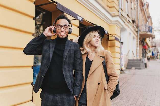 Cara africano engraçado ouvindo música em fones de ouvido ao lado de uma linda garota loira. mulher de cabelos loiros caucasiana em pé perto de homem mulato sorridente em traje preto.