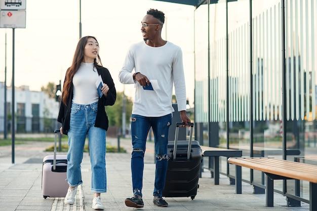 Cara africano feliz com sua mulher asiática sorridente segurando passaportes com ingressos e carregando malas perto do aeroporto.