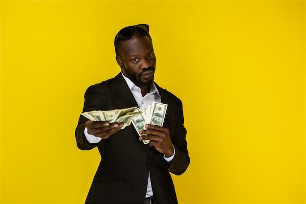 Cara afro-americana está segurando muito dinheiro com as duas mãos e olha na frente dele