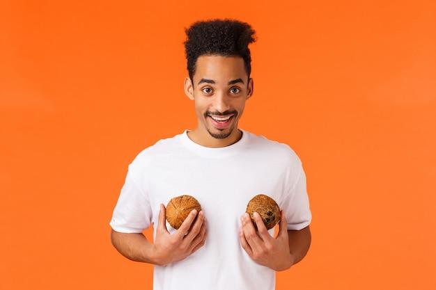 Cara afro-americana segurando cocos