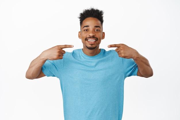 Cara afro-americano alegre de camiseta azul apontando os dedos para o sorriso branco perfeito, sorrindo depois da clínica odontológica, em pé no estúdio