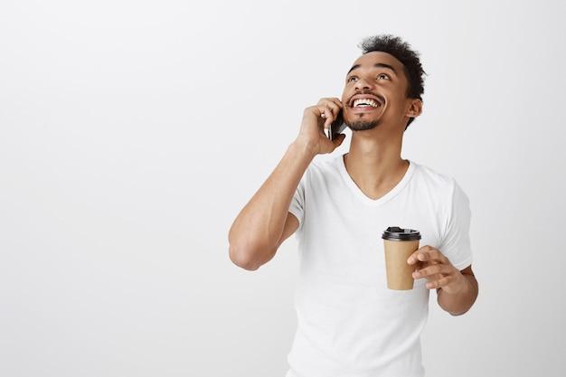 Cara afro-americano alegre falando no telefone, sorrindo feliz e bebendo café, olhando para cima