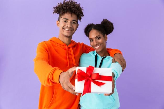 Cara afro-americano e garota sorrindo, segurando uma caixa de presente juntos, isolada sobre a parede violeta
