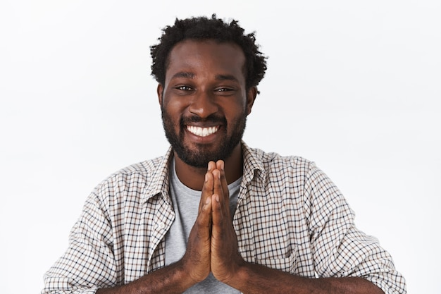 Cara afro-americano fofo pedindo algum favor, implorando ou implorando por ajuda com um sorriso terno e esperançoso