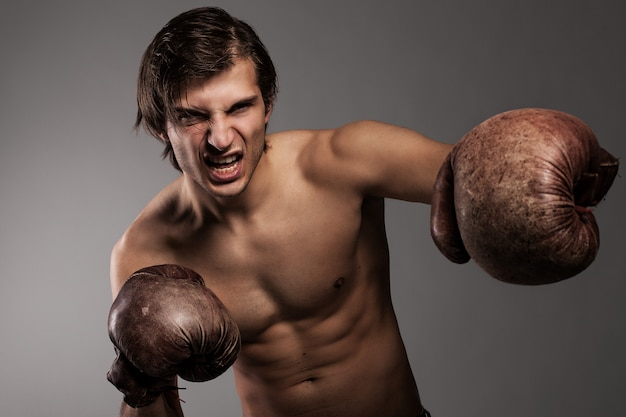 Cara agressiva em uma luvas de boxe