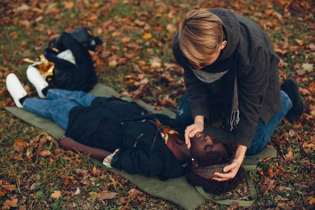 Cara ajuda uma mulher. a garota afro está inconsciente. prestando primeiros socorros no parque