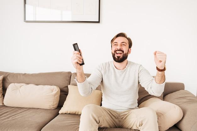 Cara alegre animada com barba e bigode, regozijando-se com a vitória do time de futebol, enquanto assiste tv no sofá com controle remoto nas mãos