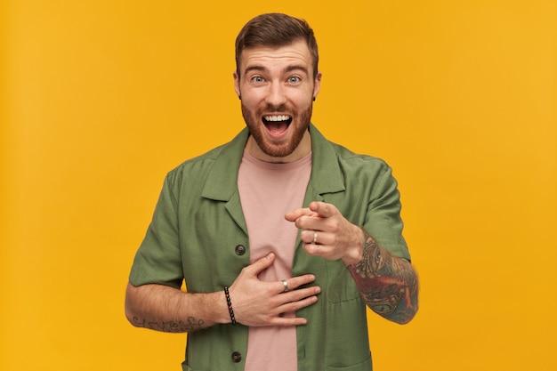 Cara alegre com barba e cabelo moreno. jaqueta verde de mangas curtas. tem tatuagem. apontando o dedo para você e segurando uma gargalhada. isolado sobre a parede amarela