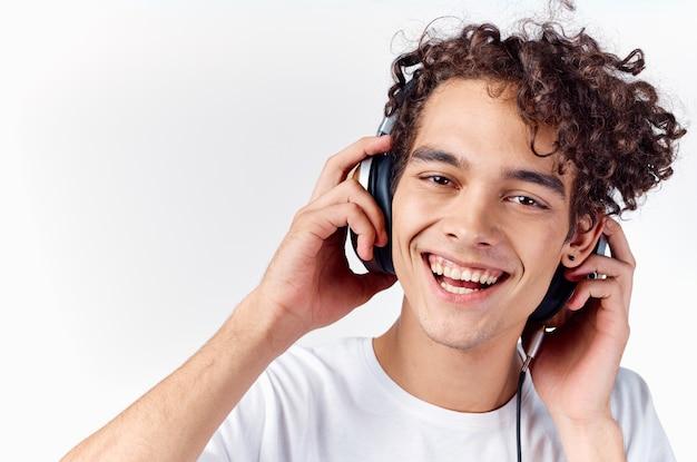 Cara alegre com cabelo cacheado, fones de ouvido, tecnologia, música, emoções