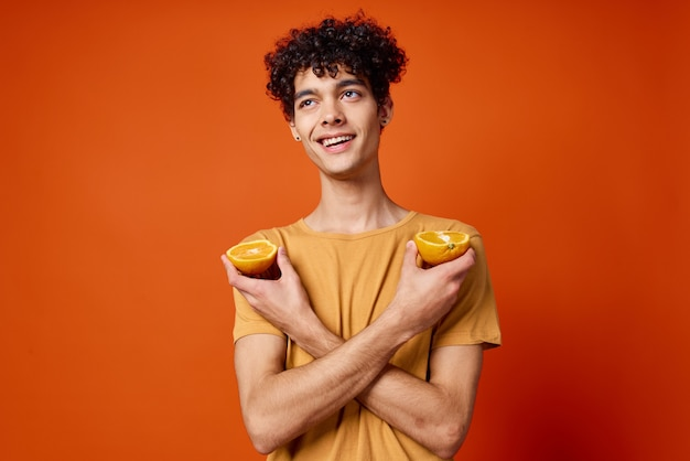 Cara alegre com cabelo encaracolado e segurando uma laranja isolada
