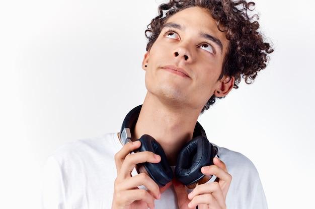 Cara alegre com cabelo encaracolado, fones de ouvido, tecnologia, música, emoções