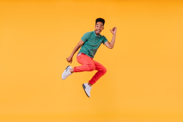 Cara alegre de cabelos curtos pulando. foto interna da deslumbrante modelo masculino em t-shirt verde se divertindo.