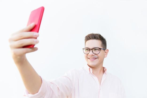 Cara alegre de óculos, segurando o telefone móvel vermelho