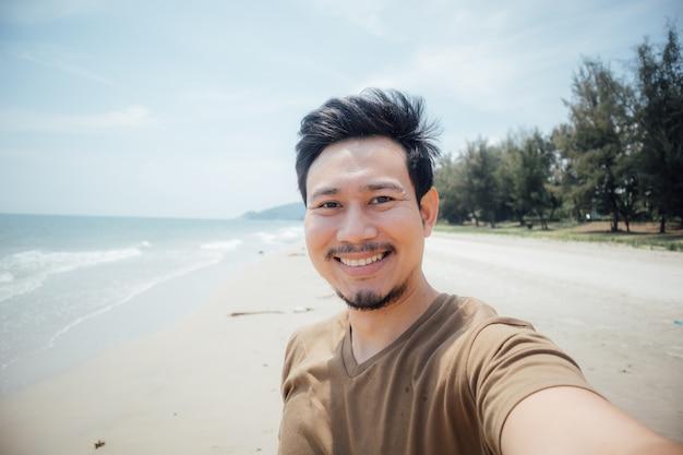 Cara alegre e feliz do selfie do homem ele mesmo na praia.