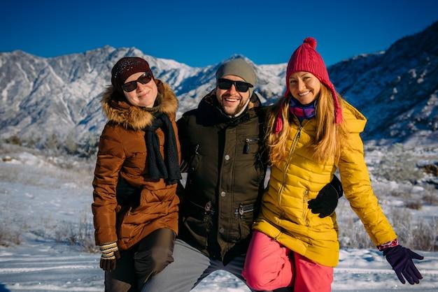 Cara alegre e garotas bonitas posando em roupas de inverno colorida