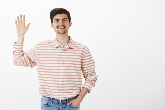 Cara alegre e satisfeita dizendo olá. foto de um jovem europeu barbudo com bigode em uma camisa listrada, levantando a mão e acenando para um amigo, fazendo um gesto de saudação, em pé sobre a parede cinza