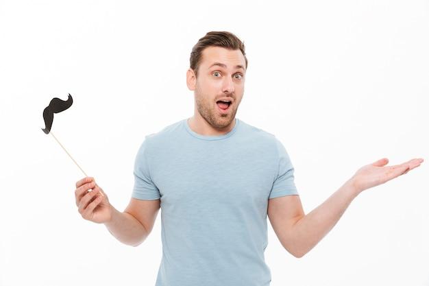 Cara alegre em camiseta casual, segurando o bigode de papel na vara e gesticulando