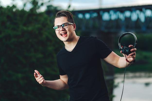 Cara alegre em copos com fones de ouvido na mão ao ar livre