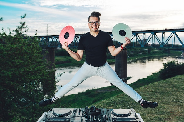 Cara alegre engraçado pulando com discos de vinil nas mãos